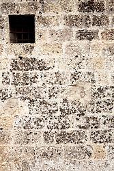 Reportage sul comune di Alessano per il progetto propugliaphoto..Piccola apertura nella muratura in pietra tufacea della masseria fortificata di Santa Lucia..Macurano è un villaggio rupestre considerato un luogo di scambio e commercio, simbolo della cultura dell'olio per la presenza ad oggi di alcune tracce nelle grotte e di frantoi funzionanti nella zona. L'insediamento è caratterizzato da una serie di grotte sia naturali che scavate nel calcare, cisterne per la raccolta dell'acqua, sistemi di canalizzazione che scendono da Montesardo, viottoli, scalette e vie più larghe con antiche tracce di carri..Si ritiene che in questo sito, un vero e proprio centro abitato ben organizzato distante circa quattro km dalla costa, i monaci basiliani scappati dall'oriente in seguito alla lotta iconoclasta, trovarono rifugio e si dedicarono all'agricoltura..L'area del villaggio rupestre fu sicuramente sfruttata in epoche successive, lo prova l'esistenza di ben tre masserie di cui una fortificata e i resti di una serie di costruzioni che fanno parte dei numerosi esempi di architettura rurale presenti in questo territorio. .Il complesso masserizio, denominato Macurano, edificato probabilmente nel Cinquecento include la Masseria di Santa Lucia e la cappella di Santo Stefano. La Masseria è dominata dal nucleo originario, ovvero dalla torre cinquecentesca coronata da beccatelli a sostegno del parapetto aggettante del terrazzo sommitale.
