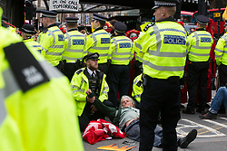 Metropolitan Police officers prepare to arrest an environmental activist from Extinction Rebellion lying in the road close to a vintage bus which was used to block a junction to the south of London Bridge on the ninth day of their Impossible Rebellion protests on 31st August 2021 in London, United Kingdom. Extinction Rebellion are calling on the UK government to cease all new fossil fuel investment with immediate effect.