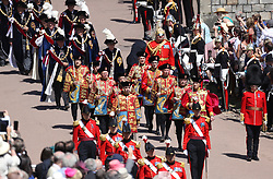 Military Knights of Windsor and other guards walk before The Knights of the Garter during the annual Order of the Garter Service at St George's Chapel, Windsor Castle.