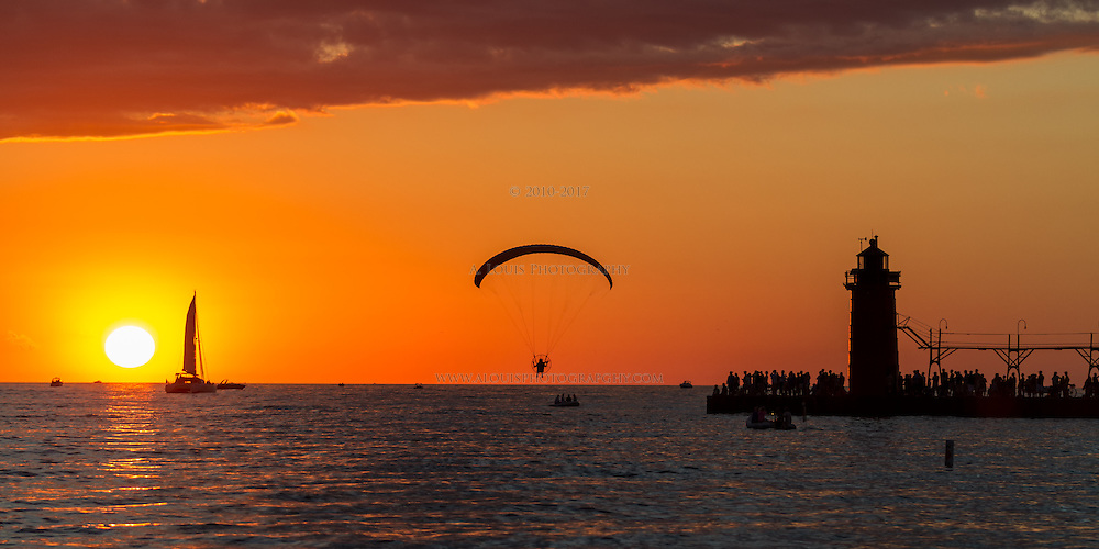 People on boats, hanging from parachutes and standing on the pier all enjoying a summer sunset in South Haven