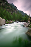 A bend of the Orco river, the main water stream of the Gran Paradiso National Park on the Piedmont side, Italy. Taken an overcast evening at the beginning of june, with some light rain. The purple glow in the sky comes from lightning behind the clouds, recorded thanks to the very long exposure used to take this scene.
