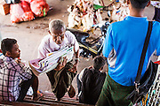17 JUNE 2013 - YANGON, MYANMAR: A newspaper vendor on the Yangon-Dala cross river ferry. The Burmese newspaper industry has enjoyed explosive growth this year after private ownership was allowed in 2013. Private newspapers were shut down under former Burmese leader Ne Win in the early 1960s. The revitalized private press is a sign of the dramatic changes sweeping Myanmar, formerly Burma, in the last three years.      PHOTO BY JACK KURTZ