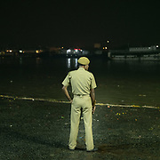 A policeman watching over the Hooghly River, traditionally called 'Ganga', and also called Kati-Ganga, a distributary of the Ganges River.