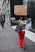 Young woman carrying a cardboard box, balanced on her head as she walks along a central London street.