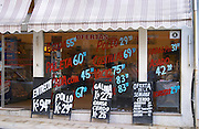 A butcher's shop selling meat and poultry chicken, with lots of publicity on the window painted in red and blue letters and on chalk boards in white standing on the pavement. Montevideo, Uruguay, South America