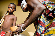 An elderly woman spreads a concoction of ground millet and water - a symbol of protection - on the body of young girls from the Krobo tribal group undergo puberty rites - locally called dipo - in Somanya, Eastern Region, Ghana.