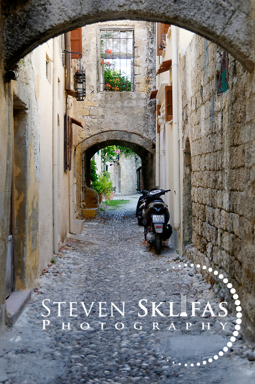 Rhodes Greece. Quite narrow arched pebbly alleyway at the old walled medieval town of Rhodes. The old town is a UNESCO world heritage listed site and the best preserved, oldest and largest living medieval city in Europe. The 4km defensive walls were built by the Knights of St John during the 13th to 15th century to defend Western Europe against the expanding Ottoman Empire. Within the walls are a medieval warren of small alleyways and magnificent historical buildings. The island of Rhodes is the largest of the Dodecanese Island group and one of the most popular Greek Islands.