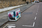 A chest freezer apparently from a shop selling ice creams, has been fly-tipped in a parking bay of a residential street, on 1st January 2019, in Herne Hill, south London, England.