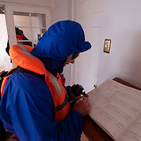A tourist signs guest book in lighthouse at Cape Horn, Tierra del Fuego, Chile, southernmost tip of South America.