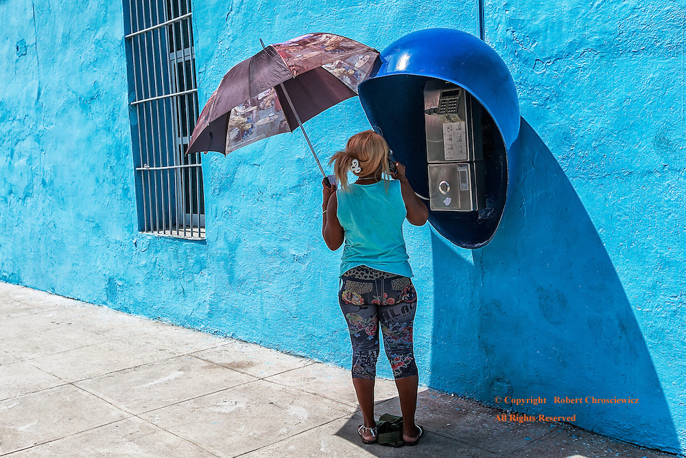 Phone Call: A woman makes a telephone call beside a deep blue wall, with the line of the base of the wall and the shadow of the phone booth converge in the corner of the photograph, Cienfuegos Cuba.