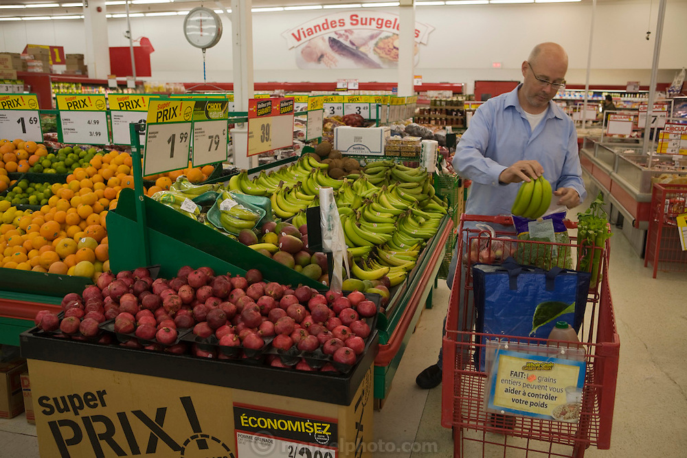 "Kirk Finken does the weekly shopping for the family. The Finken family live in a suburban straw bale home. They live a block-and-a-half east of Lac Deschênes in the city of Gatineau*, Quebec. ""At the bigger markets,"" says Kirk, ""everything is so seductive that you end up spending more money (than you intended)"". He sees it as consumer manipulation."
