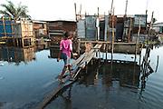 A girl walks up to a latrine on stilts in the Clara town slum in Monrovia, Montserrado county, Liberia on Thursday April 5, 2012.