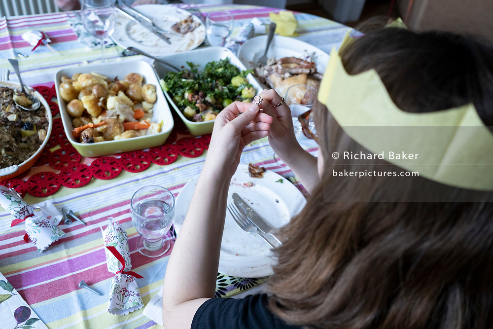 A young woman tries to solve a cracker novelty puzzle after a family lunch on Christmas Day, on 25th December 2020 in London, England.