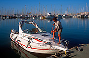 A boat owner washes the deck of his small pleasure boat in the Marina, on 21st June 2001, in Palma, Mallorca, Balearic Islands, Spain.