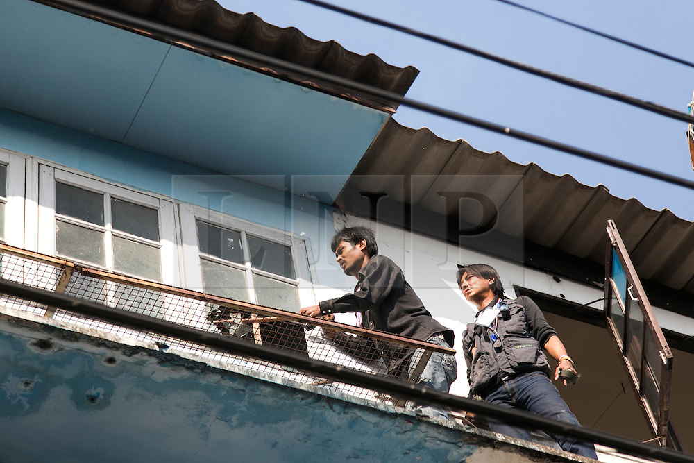 © Licensed to London News Pictures. 17/01/2014.  An Anti-Government protestor smashes a window in an abandoned apartment complex in search for the suspect whom threw an explosive device injuring eight people during an anti-government street rally on January 17, 2014 in Bangkok, Thailand. Anti-government protesters launch 'Bangkok Shutdown', blocking major intersections in the heart of the capital, as part of their bid to oust the government of Prime Minister Yingluck Shinawatra ahead of elections scheduled to take place on February 2. Photo credit : Asanka Brendon Ratnayake/LNP