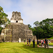 A group of tourists in the Main Plaza in front of the Temple of the Masks, or Temple 2, in the Tikal Maya ruins in northern Guatemala, now enclosed in the Tikal National Park. Visitors can climb to near the top of the pyramid using wooden stairs that have been constructed at left of the building.