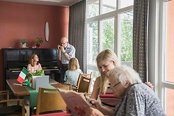 Woman reading newspaper with her mother while father is blowing harmonica, Eichenau, Bavaria, Germany