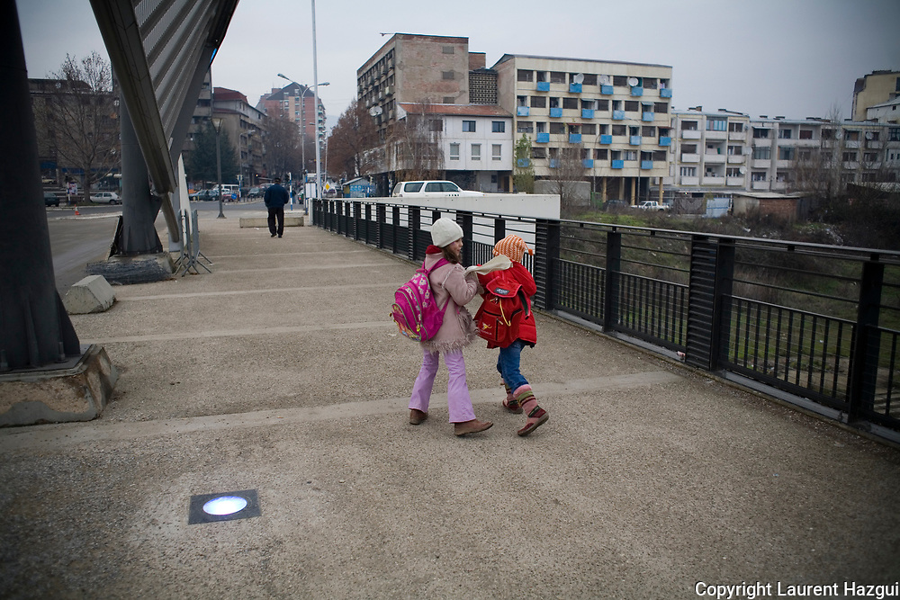0112007. Mitrovica. The albanian girls living in the north of Mitrovica. The bridge is the symbol of the conflict between Albanians and Serbians about the independence of Kosovo. The Serbs live in the north of the town while the Albanians live in the south. KFOR secure the crossing of the bridge.