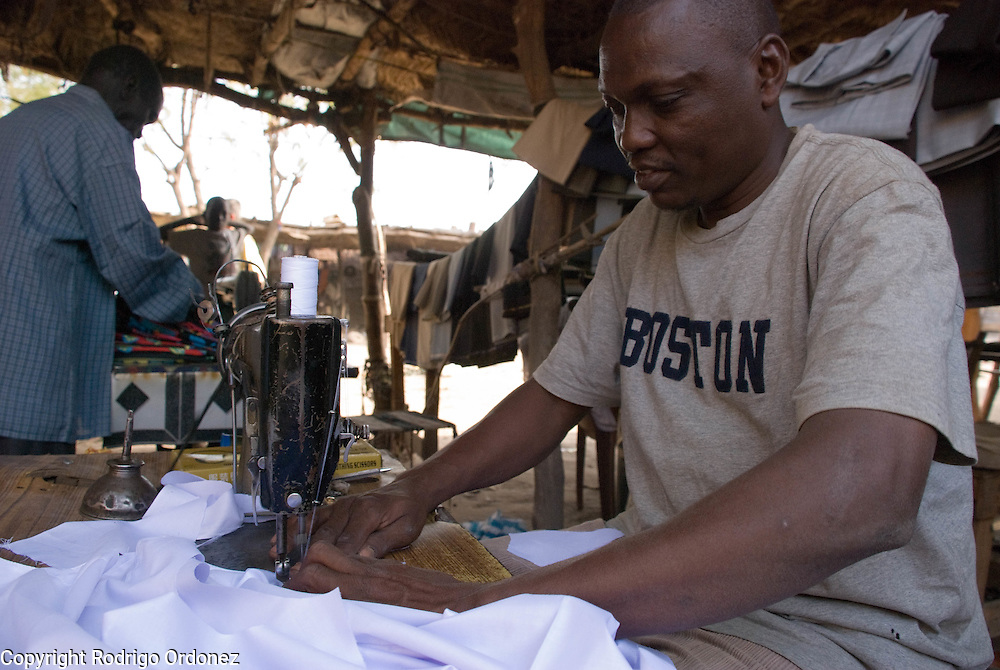 A worker sews clothes at a tailoring workshop in the market of Abyei.