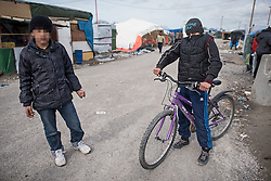 © London News Pictures. 29/04/2016. Calais, France. 11 year-old Unaccompanied child refugee Afghan boy Azim (right) riding his bike in the calais Jungle. David Cameron has announced Britain will take in some child refugees living in camps inside the EU. Photo credit: Ben Cawthra/LNP