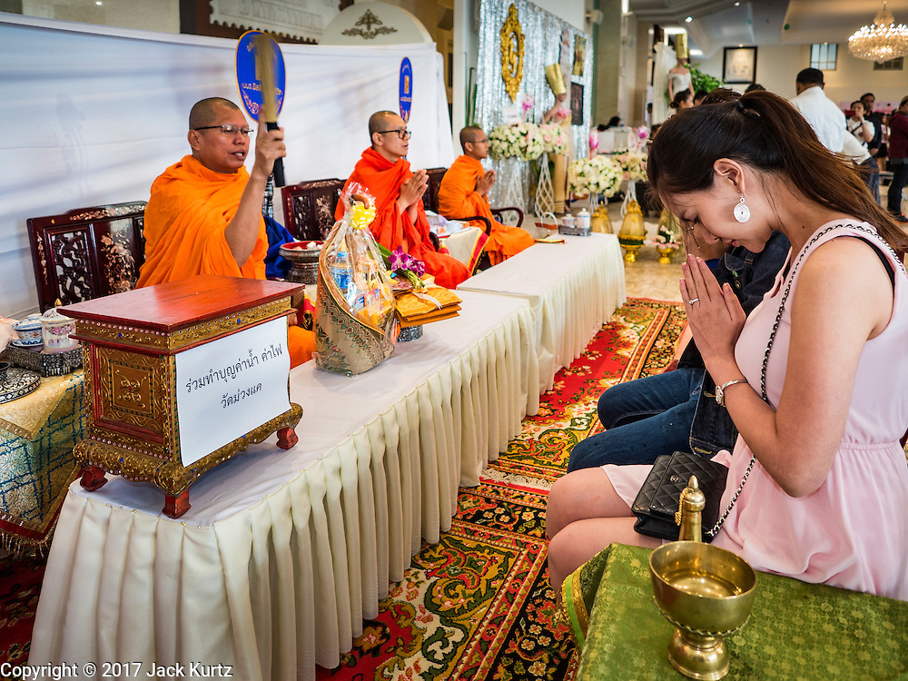"""14 FEBRUARY 2017 - BANGKOK, THAILAND:  Buddhist monks bless a couple's marriage during a mass wedding in the Bang Rak district in Bangkok. Bang Rak is a popular neighborhood for weddings in Bangkok because it translates as """"Village of Love."""" (Bang translates as village, Rak translates as love.) Hundreds of couples get married in the district on Valentine's Day, which, despite its Catholic origins, is widely celebrated in Thailand.     PHOTO BY JACK KURTZ"""