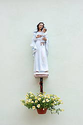 Statue of Madonna on church in village of Burano in Venice Italy