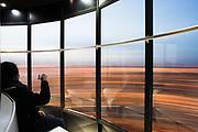 Bezoekster van de Euromast kijkt naar het uitzicht over Rotterdam vanuit de roterende lift.