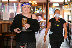 © Licensed to London News Pictures. 26/10/2020. London, UK. A barmaid wearing a face shield takes a drink to a customer in a Wetherspoons pub in north London. The hospitality industry estimates that pubs, bars and restaurants have spent £900million on screens, masks and hand sanitisers to make their venues safe for reopening, following the easing of COVID-19 lockdown restrictions. It has been reported that each pub has spent more than £10,000 adapting the interiors of their venues but with the latest restrictions, many now only serve customers outside their premises. Wetherspoons has spent £13.1million on getting its 875 pubs ready. Photo credit: Dinendra Haria/LNP