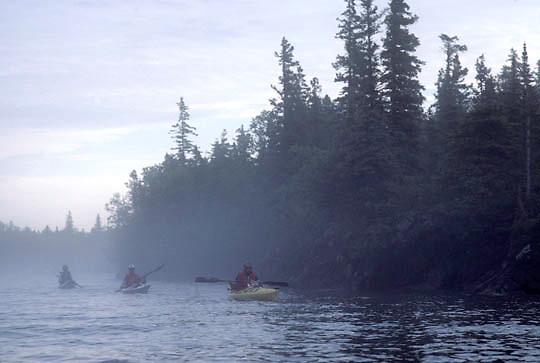 Isle Royale National Park, kayakers paddling in fog off of Amygdaloid Island.  Michigan.