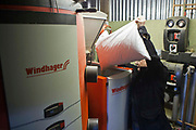 A man refuels a Windhager biomass boiler with wood chip. Llanerchaeron, Wales, UK. Biomass fuel is a renewable energy source, made up of certain biological materials, such as wood, hemp or sugarcane. It is therefor a sustainable form of producing energy. It is also an inexpensive fuel, as it is usually made up of rejected materials.