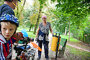 Friendly Polish woman park attendant age 55 conversing with bikers. Paderewski Park Rzeczyca Central Poland