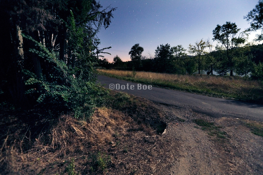 end of dirt path with light from full moon