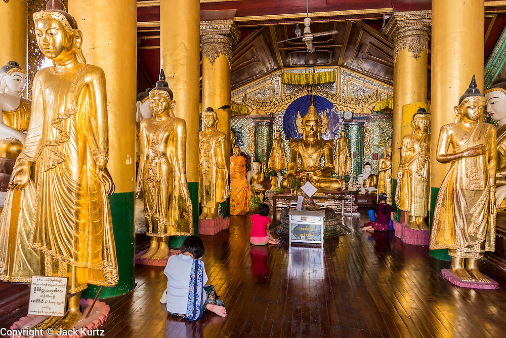15 JUNE 2013 - YANGON, MYANMAR:  People pray in a hall of Buddha statues at Shwedagon Pagoda. Shwedagon Pagoda is officially known as Shwedagon Zedi Daw and is also called the Great Dagon Pagoda or the Golden Pagoda. It is a 99 meter (325 ft) tall pagoda and stupa located in Yangon, Burma. The pagoda lies to the west of on Singuttara Hill, and dominates the skyline of the city. It is the most sacred Buddhist pagoda in Myanmar and contains relics of the past four Buddhas enshrined: the staff of Kakusandha, the water filter of Koṇāgamana, a piece of the robe of Kassapa and eight strands of hair from Gautama, the historical Buddha. Burmese believe the pagoda was established as early ca 540BC, but archaeological suggests it was built between the 6th and 10th centuries. The pagoda has been renovated numerous times through the centuries. Millions of Burmese and tens of thousands of tourists visit the pagoda every year, which is the most visited site in Yangon. PHOTO BY JACK KURTZ