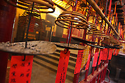 A row of incense burning trays inside a temple in Hong Kong