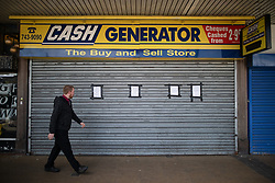 © Licensed to London News Pictures .  07/05/2020 . Salford, UK. A man walks past a shuttered branch of Cash Convertor on Hankinson Way in Salford . Photo credit : Joel Goodman/LNP