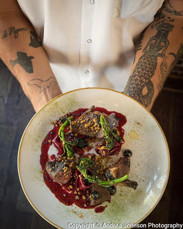 Gabriel Rucker, chef & owner, holding pigeon dish, Le Pigeon restaurant, Portland, Oregon