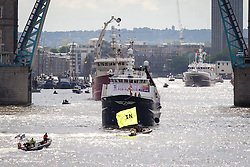 © Licensed to London News Pictures. 15/06/2016. London, UK. Counter protestors fly an 'In' flag as the pro-Brexit campaign 'Fishermen for Leave', sail a flotilla of over 30 vessels up the Thames. The flotilla, including UKIP leader Nigel Farage, caused traffic issues in central London, as vessels travelled up the Thames for high tide and to coincide with the last Prime Minister's Questions before the EU referendum takes place on 23 June. Photo credit : Tom Nicholson/LNP