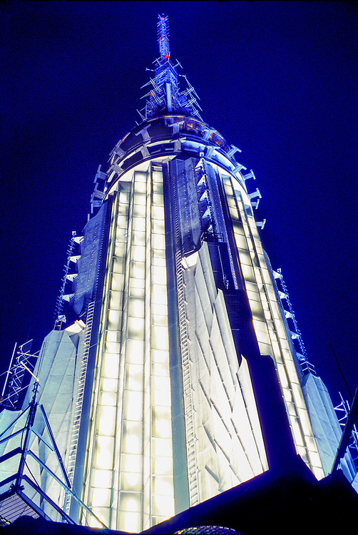 Against a deep blue, night sky is the illuminated, rocketship-like, Art Deco spire of the Empire State Building festooned with dozens of high-powered broadcasting antennas.