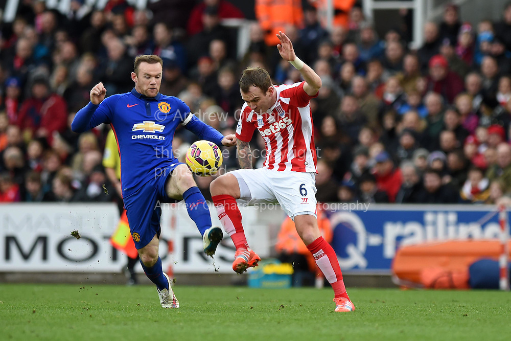 Glen Whelan of Stoke city ® challenges Wayne Rooney of Man Utd.  Barclays Premier league match, Stoke city v Manchester Utd at the Britannia Stadium in Stoke on Trent, Staffs on New Years Day , Thursday 1st Jan 2015. pic by Andrew Orchard. Andrew Orchard sports photography.