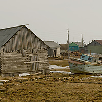 North of the Arctic Circle in Russia, an old boat sits amongst sheds and houses in Snopa village, close to the Arctic Ocean coast.