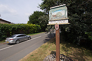 Photo by Andrew Tobin/Tobinators Ltd - 07710 761829 - Witcham village signpost outside the village centre during the World Peashooting Championships held at Witcham, Cambridgeshire, UK on 13th July 2013. Run in conjunction with the village fair, the Championships have been held in Witcham since 1971 when they were started by a Mr Tyson, the village schoolmaster, in order to raise funds for the village hall.Competitors come from as far afield as the USA and New Zealand to attempt to win the event. The latest technology is often used, including laser sights and titanium and carbon fibre peashooters. All peashooters must conform to strict length rules, not exceeding 12 inches, and have to hit a target 12 feet away. Shooting 5 peas at a plasticine target attached to a hay bale, the highest scorers move through the initial rounds to a knockout competition, followed by a sudden death 10-pea shootout.