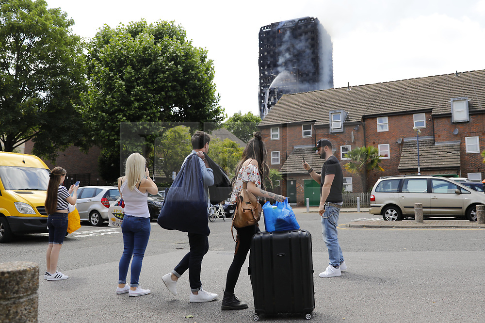 © Licensed to London News Pictures. 14/06/2017. London, UK. Residents evacuate as the Grenfell Tower fire still is not under control 14 hours after the fire broke in west London on 14 June 2017. Photo credit: Tolga Akmen/LNP