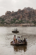 River crossing with traditional boats at the UNESCO heritage site, ancient, holy village and Temple complex of Hampi on 5th December 2009, Karnataka, India. Hampi is one of Indias most famous landmarks, with numerous Hindu temples from the Vijayanagara Empire. .