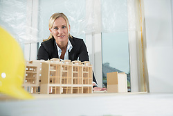 Female architect with architectural model at construction site