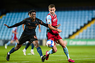 Nathaneal Ogbeta of Man City u21 Ryan Colclough (7) of Scunthorpe United battles for possession with during the EFL Trophy match between Scunthorpe United and Manchester City at Glanford Park, Scunthorpe, England on 29 September 2020.