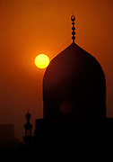 Egypt, 2000 - Sunset with domed Cairo Mosque. The setting sun silhouettes the spire of an Islamic mosque against an deep orange sky.