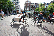 In Utrecht rijdt een fietskoerier met een bakfiets over de Oudegracht.<br /> <br /> In Utrecht a bike courier is cycling on a cargo bike.
