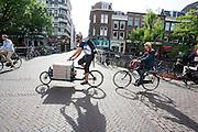 In Utrecht rijdt een fietskoerier met een bakfiets over de Oudegracht.<br /> <br /> In Utrecht a bike courier is cycling on a cargo bike.