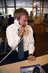 Man with cerebral palsy working as technical assistant in visual communications office; talking on telephone,