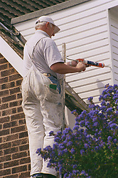 Painter and decorator working on exterior of house,